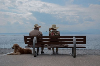 Old-elderly-couple-sitting-on-bench-by-beach